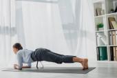 krásná podnikatelka cvičit jógu v prkně na podložce v kanceláři
