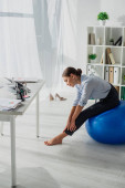professional businesswoman stretching on fitness balls in office
