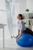 happy businesswoman exercising on fitness balls in office