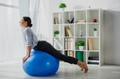 happy businesswoman stretching on fitness balls in office
