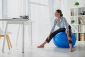 smiling businesswoman exercising on fitness balls in office