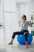 beautiful happy businesswoman exercising on fitness balls in office