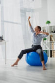 beautiful happy businesswoman stretching on fitness balls in office