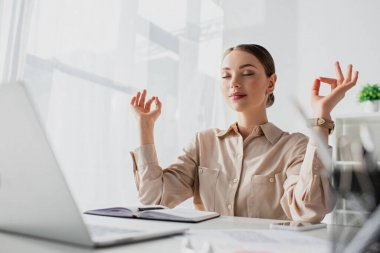 beautiful businesswoman meditating with closed eyes and gyan mudra at workplace with laptop