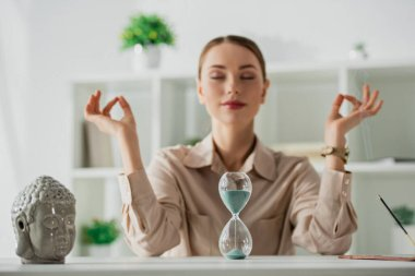 selective focus of businesswoman meditating with closed eyes and gyan mudra at workplace with Buddha head, sand clock and incense stick