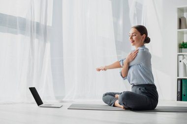 young businesswoman having online classes on laptop and stretching hands in lotus position on mat in office