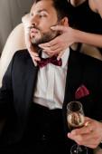 abgeschnittene Ansicht einer Frau, die das Gesicht eines gutaussehenden Mannes berührt, der ein Glas Champagner hält