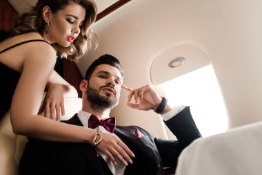 Low angle view of sexy woman touching chest of elegant, confident man in plane stock vector