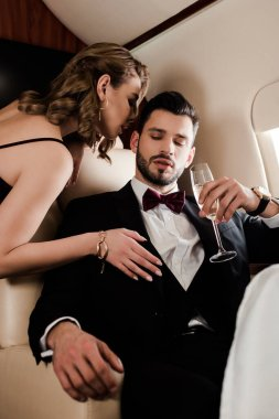 sensual woman touching elegant man holding glass of champagne in plane