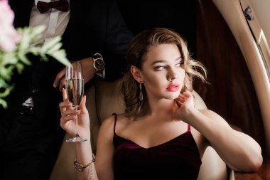 cropped view of man standing near pensive, beautiful woman holding glass of champagne in plane