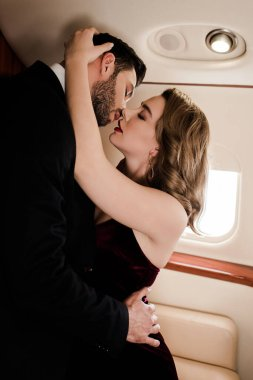 handsome man hugging and kissing sexy, elegant woman in plane