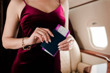 Cropped view of sexy woman in elegant dress holding passport and air ticket stock vector