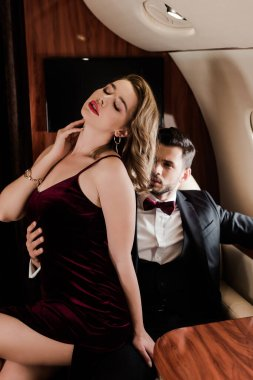 handsome man touching sexy, elegant woman sitting on his laps in plane