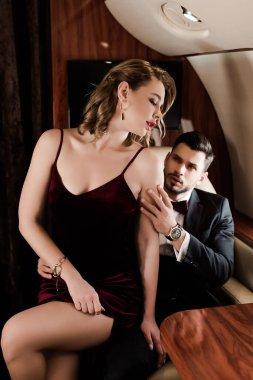 seductive, elegant woman sitting on laps of handsome man in plane