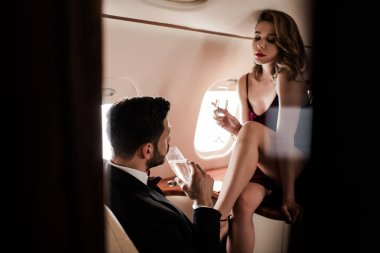 selective focus of passionate woman with champagne glass sitting on table opposite man in plane