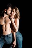 sinnliches Mädchen umarmt hemdlosen, muskulösen Freund isoliert auf schwarz