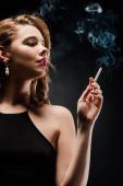 csábító, elegáns nő néz félre, miközben tartja cigaretta fekete háttér