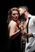 sexy Mann im aufgeknöpften Hemd küsst elegantes, leidenschaftliches Mädchen, das Champagnerglas isoliert auf schwarz hält