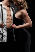 abgeschnittene Ansicht von sexy Mann in aufgeknöpftem Hemd umarmt elegantes, verführerisches Mädchen isoliert auf schwarz