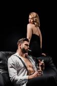 Fotografie attraktive, elegante Frau sitzt auf der Rückseite des Sofas neben sexy Mann mit Champagnerglas und raucht isoliert auf schwarz