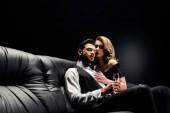 Fotografie attraktive, sexy Frau umarmt gutaussehenden, eleganten Mann sitzt auf Ledersofa mit Champagnerglas auf schwarz