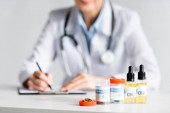 selective focus of dried marijuana, bottles with cbd and medical cannabis lettering near doctor writing prescription