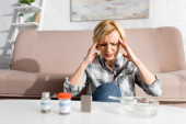selective focus mature woman having migraine near bottles with medical cannabis and ashtray