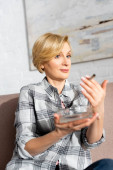 selective focus of surprised mature woman holding joint with legal marijuana and ashtray