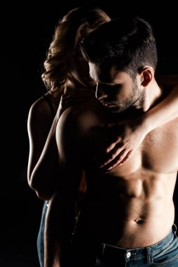 young woman embracing shirtless, muscular boyfriend isolated on black
