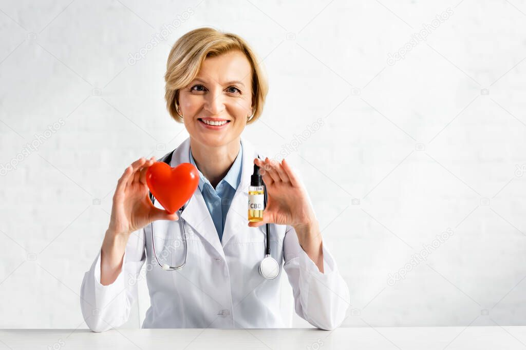 Cheerful and mature doctor holding bottle with cbd lettering and red heart in clinic stock vector