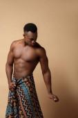 szexi meztelen törzsi afro férfi borított takaró pózol bézs
