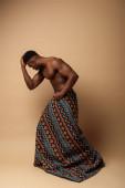 Sexy nahý kmenový afro muž pokrytý dekou pózující na béžové
