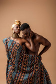 sexy naked tribal afro woman covered in blanket posing near man on beige