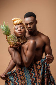 sexy naked tribal afro woman covered in blanket posing with pineapple near man on beige