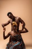 szexi meztelen törzsi afro nő borított takaró pózol közel férfi bézs