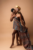 Photo sexy naked tribal afro woman covered in blanket posing near man on beige