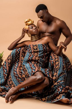 Sexy naked tribal afro woman covered in blanket posing near man on beige stock vector