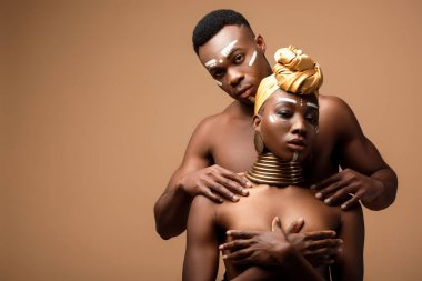 Naked tribal afro couple posing on beige background stock vector