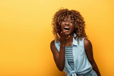 Happy african american woman laughing on yellow background stock vector