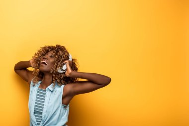 Happy african american woman listening music in headphones on yellow background stock vector