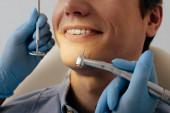 Fotografie ostříhaný pohled zubaře v latexových rukavicích držících zubní nástroje poblíž veselého pacienta