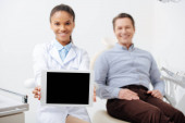 selective focus of smiling african american dentist holding digital tablet with blank screen near happy patient