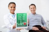 Selektiver Fokus des fröhlichen afrikanisch-amerikanischen Zahnarztes, der ein digitales Tablet mit Herzfrequenz und Puls auf dem Bildschirm in der Nähe eines glücklichen Patienten hält