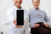 selektivní zaměření veselý africký americký zubař držící smartphone s prázdnou obrazovkou poblíž šťastný pacient