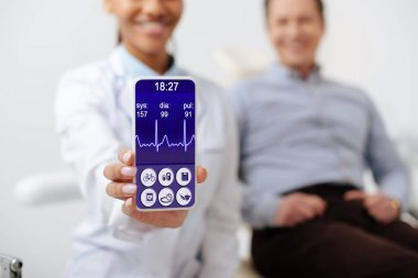 Selective focus of cheerful african american dentist holding smartphone with medical app on screen near happy patient stock vector