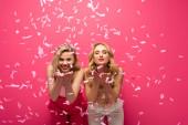 Lächelnde blonde Mädchen blasen Luftküsse in die Kamera unter fallendem Konfetti auf rosa Hintergrund