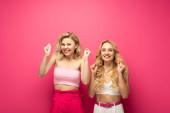 Boldog szőke nők bemutató igen gesztus rózsaszín háttér