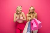 Veselé blondýny dívka dívá na přítele držící nákupní tašky na růžovém pozadí