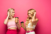 Photo Pensive blonde sisters holding coffee to go on pink background
