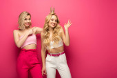 Fotografie Smiling girl pointing on positive blonde friend in crown on pink background